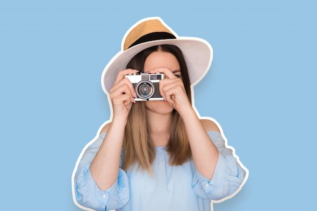 Lustiges kühles mädchen mit tragendem hut der retro- kamera, blaues kleid über blau