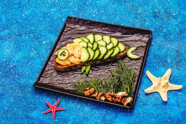 Lustiges lachssandwich mit gurke in fischform Premium Fotos