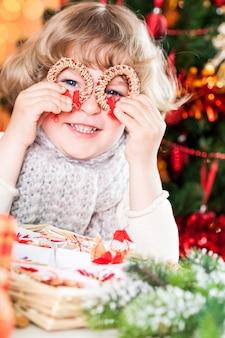 Lustiges lächelndes kind, das handgemachte öko-dekorationen gegen weihnachtsbeleuchtung hält