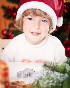 Lustiges lächelndes kind in weihnachtsmütze gegen weihnachtsbeleuchtung