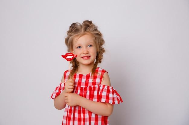 Lustiges lächelndes sommerkleid des kleinen mädchens auf weißem hintergrund. baby mit einem lippenzubehör auf einem stock.