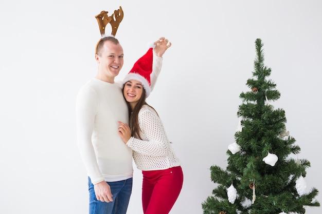 Lustiges liebendes paar nahe weihnachtsbaum. mann trägt hirschhörner und frau trägt weihnachtsmütze