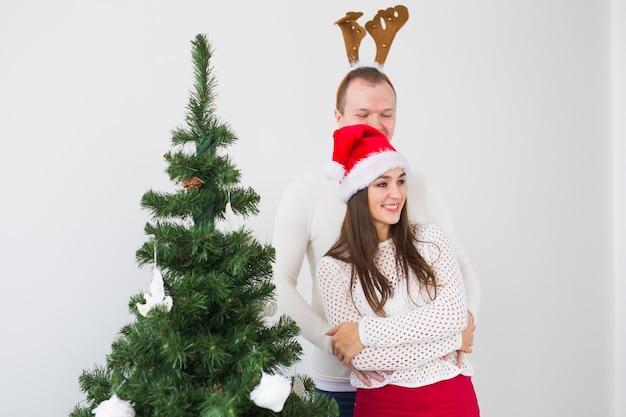 Lustiges liebevolles paar nahe weihnachtsbaum. mann trägt hirschhörner und frau trägt weihnachtsmütze.