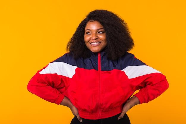 Lustiges lockiges afroamerikanermädchen gekleidet in der roten sportjacke auf gelber wand