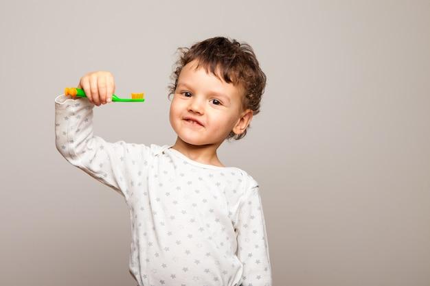 Lustiges lockiges kind steht lächelnd und hält eine zahnbürste in seinen händen. gesunde starke kinderzähne. die regeln der persönlichen hygiene.