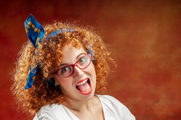Lustiges lockiges rothaariges mädchen mit brille schreit glücklich