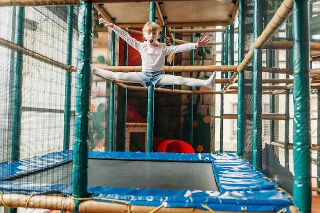 Lustiges mädchen, das auf trampolin, spielzentrum springt