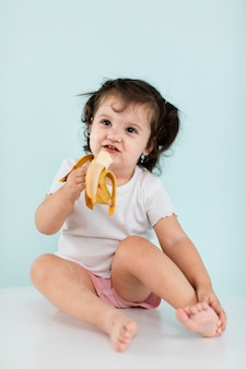 Lustiges mädchen, das banane isst
