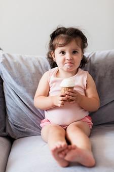 Lustiges mädchen, das eine eiscreme auf dem sofa isst