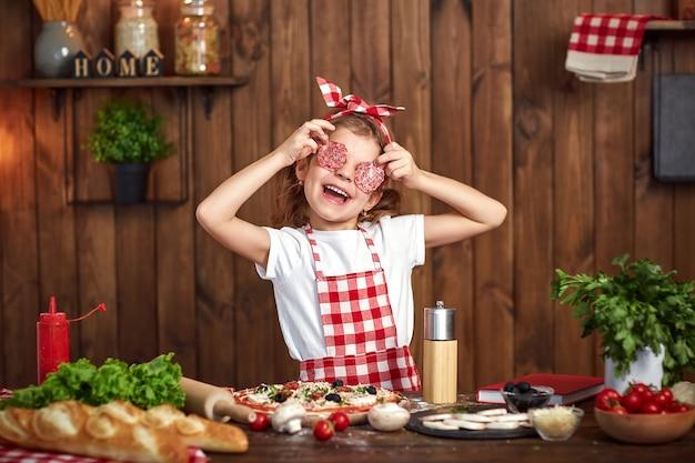 Lustiges mädchen, das pizza kocht und mit salamischeiben täuscht