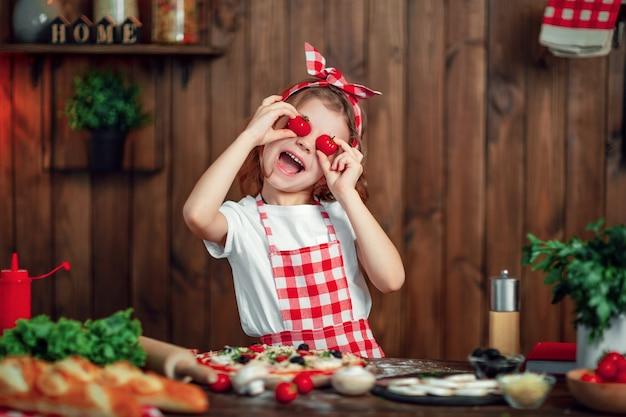 Lustiges mädchen, das pizza kocht und mit tomaten täuscht
