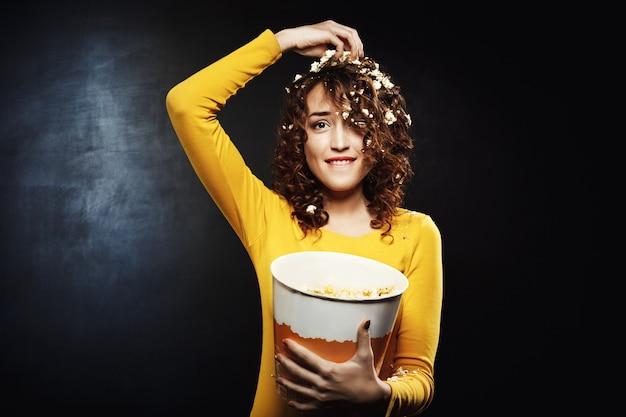 Lustiges mädchen, das popcorn isst, während shows zu hause party sieht