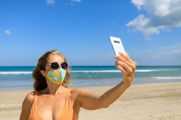 Lustiges mädchen, das selfie foto durch smartphone am tropischen meeresstrand nimmt.