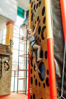 Lustiges mädchen, das wände im kinderspielzentrum klettert