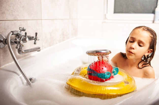 Lustiges mädchen gießt ihren kopf von einem ball und schwimmbrille von der dusche