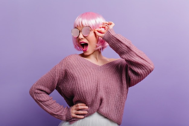 Lustiges mädchen im gestrickten pullover und im rosa peruke, die mit vergnügen tanzen. innenporträt der sorglosen dame in der perücke, die in der sonnenbrille aufwirft.