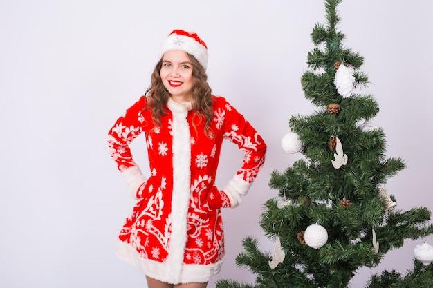 Lustiges mädchen im tragen des weihnachtsmannkostüms über weihnachtsbaum