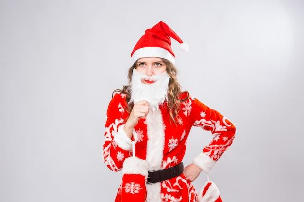 Lustiges mädchen im tragen des weihnachtsmannkostüms und des bartes über weißer wand. urlaub, witz und menschenkonzept