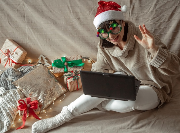 Lustiges mädchen in der weihnachtsbrille und im weihnachtsmannhut sitzt an einem laptop auf einer gemütlichen wand der weihnachtsgeschenke.