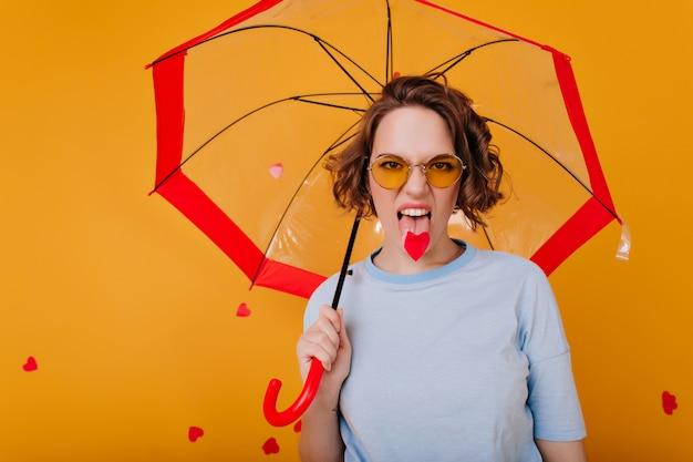 Lustiges mädchen in der weinlese-sonnenbrille, die zunge während des fotoshootings auf gelber wand zeigt. innenfoto der lockigen frau im blauen t-shirt, das unter sonnenschirm steht.