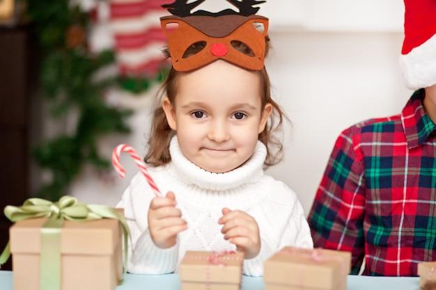 Lustiges mädchen in einer weihnachtshirschmaske, die zuckerstange in einer hand hält.