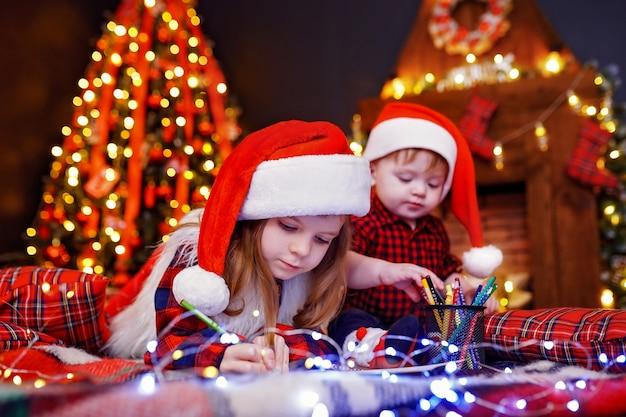 Lustiges mädchen in nikolausmütze schreibt brief an santa und ihren kleinen bruder