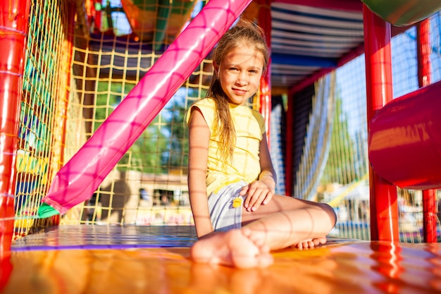 Lustiges mädchen mit tränenflecken sitzt auf einem teppich und wischt sich in einem unterhaltungszentrum mit farbenfrohen geräten die tränen ab