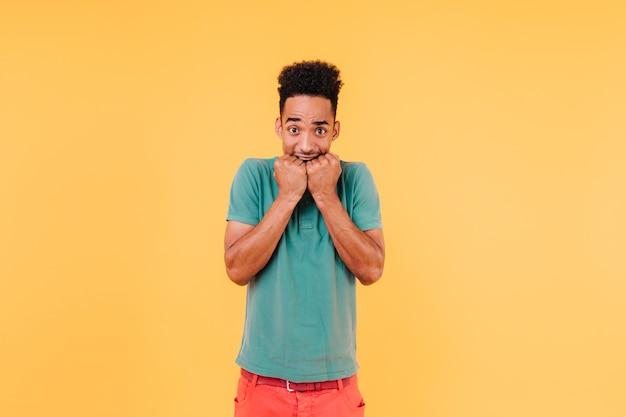 Lustiges männliches modell mit dem aufstellen des lockigen haares. raffinierter afrikanischer typ, der besorgte gefühle ausdrückt.
