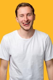 Lustiges mannporträt. unbeschwerter lebensstil. begeisterter kerl streckt die zunge heraus und lächelt isoliert auf orange.