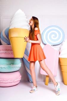 Lustiges modeporträt der hübschen blonden frau, die rieseneis hält und nahe große falsche süße, pastellfarben, schönes kleid, süßwarenladen aufwirft.