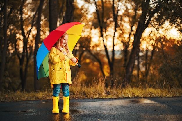Lustiges nettes kleinkindmädchen, das wasserdichten mantel mit buntem regenschirm trägt