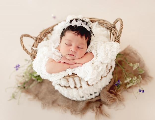 Lustiges neugeborenes im korb auf bauch