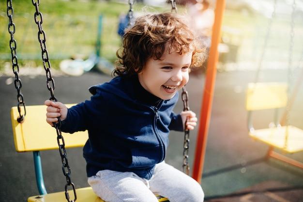 Lustiges niedliches glückliches baby, das auf dem spielplatz spielt. das gefühl von glück, spaß, freude. lächeln eines kindes.