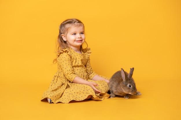 Lustiges niedliches kindermädchen im gelben kleid mit kaninchen, das auf gelbem hintergrund sitzt.