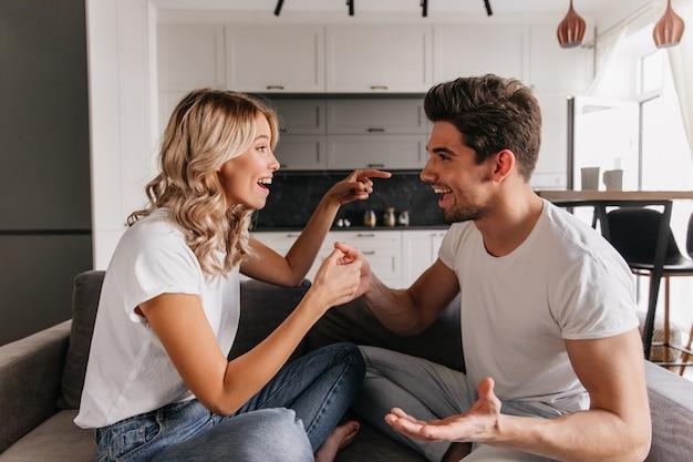 Lustiges paar, das auf sofa sitzt, einander ansieht und daumenspiel spielt. mädchen zeigt auf kerl und versucht ihn abzulenken.