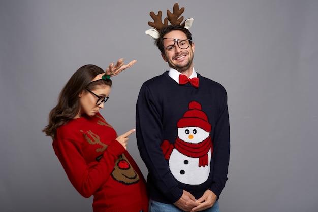 Lustiges paar, das in weihnachtskleidung aufwirft