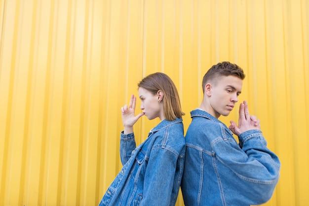 Lustiges paar, das rücken an rücken auf händchenhalten in form von waffen auf hintergrund der gelben wand steht.