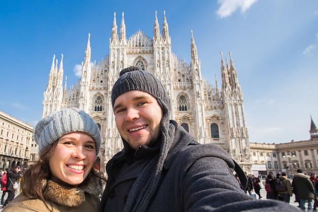 Lustiges paar, das selbstporträt auf dem domplatz in mailand im winter macht, das italien und die beziehung reist