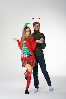 Lustiges paar, das seltsame weihnachtspullover trägt