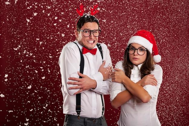 Lustiges paar, das vom kalten wetter in der weihnachtszeit zittert