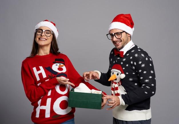 Lustiges paar, das weihnachtsgeschenk öffnet