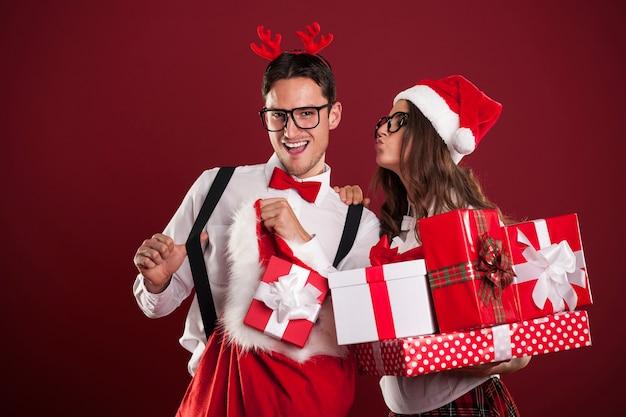 Lustiges paar mit stapel von weihnachtsgeschenken