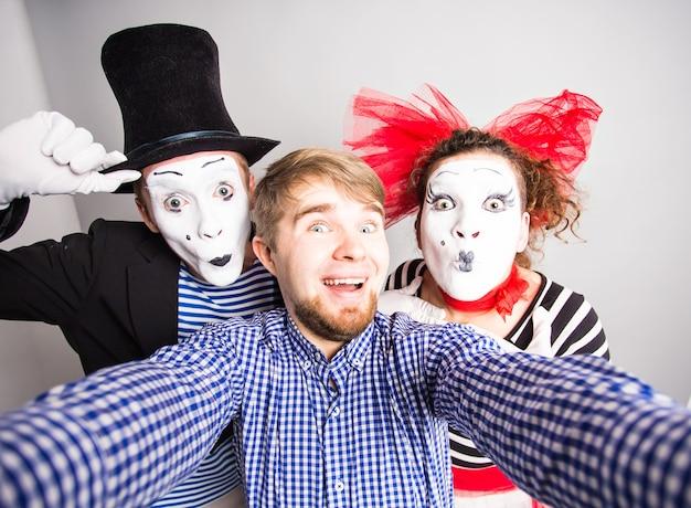Lustiges paar pantomimen, die ein selfie-foto machen, aprilscherz-konzept.