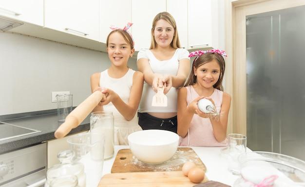 Lustiges porträt der familie, die utensilien auf die kamera in der küche zeigt