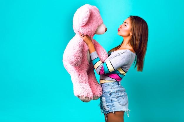 Lustiges porträt der hübschen frau, die mit großem flauschigem teddybär spielt, süße pastellfarben. halten sie ihr geschenk und senden sie einen kuss, machen sie ein lustiges gesicht, feiertage, freude, kindheit.