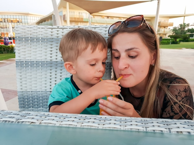 Lustiges porträt der jungen mutter mit dem kleinen jungen, der orangensaft aus zwei strohhalmen im strandcafé trinkt