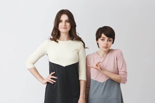 Lustiges porträt des lesbischen paares der jungen studentenmädchen in den passenden kleidern. langhaariges mädchen, das größer ist als ihre kleine freundin.