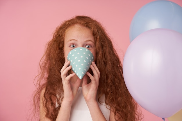 Lustiges porträt des reizenden gelockten weiblichen kindes der reizenden rothaarigen, die kamera positiv mit den geöffneten großen augen betrachtet und über rosa hintergrund mit geburtstagskappe und luftballons täuscht