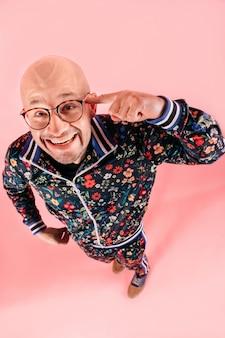 Lustiges porträt von oben genanntem des kahlen mannes in der blume druckte den trainingsanzug, der verrücktes gefühl im studio über rosa hintergrund ausdrückt.