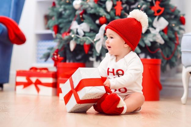 Lustiges säuglingsbaby packt weihnachtsgeschenkbox aus. frohe weihnachten und ein glückliches neues jahr.